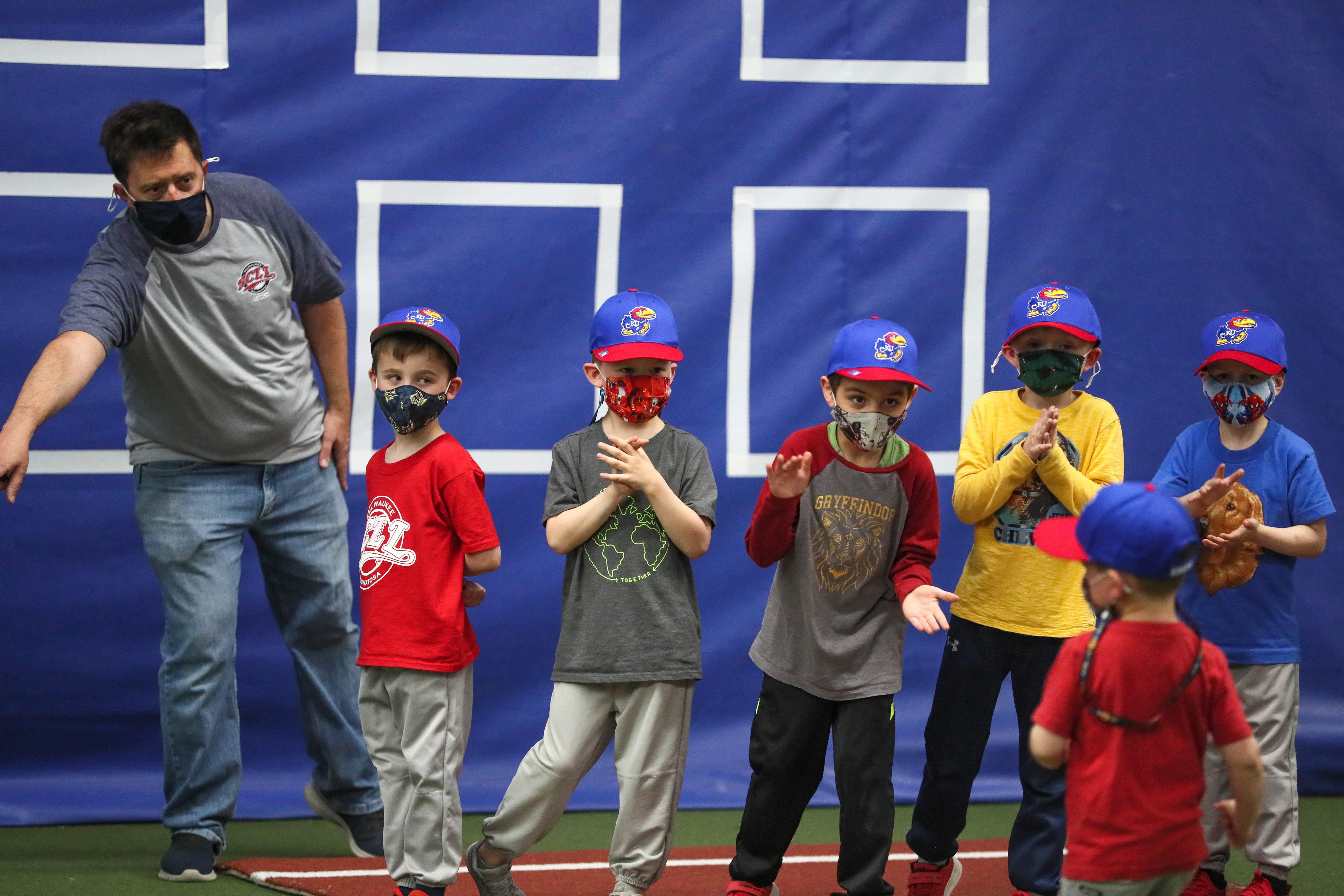 Kansas T-Ball Hawks player Matias Werstein-Aravena, 5, middle, cheers on his teammate as he runs to home plate April 22, 2021, in Milwaukee.