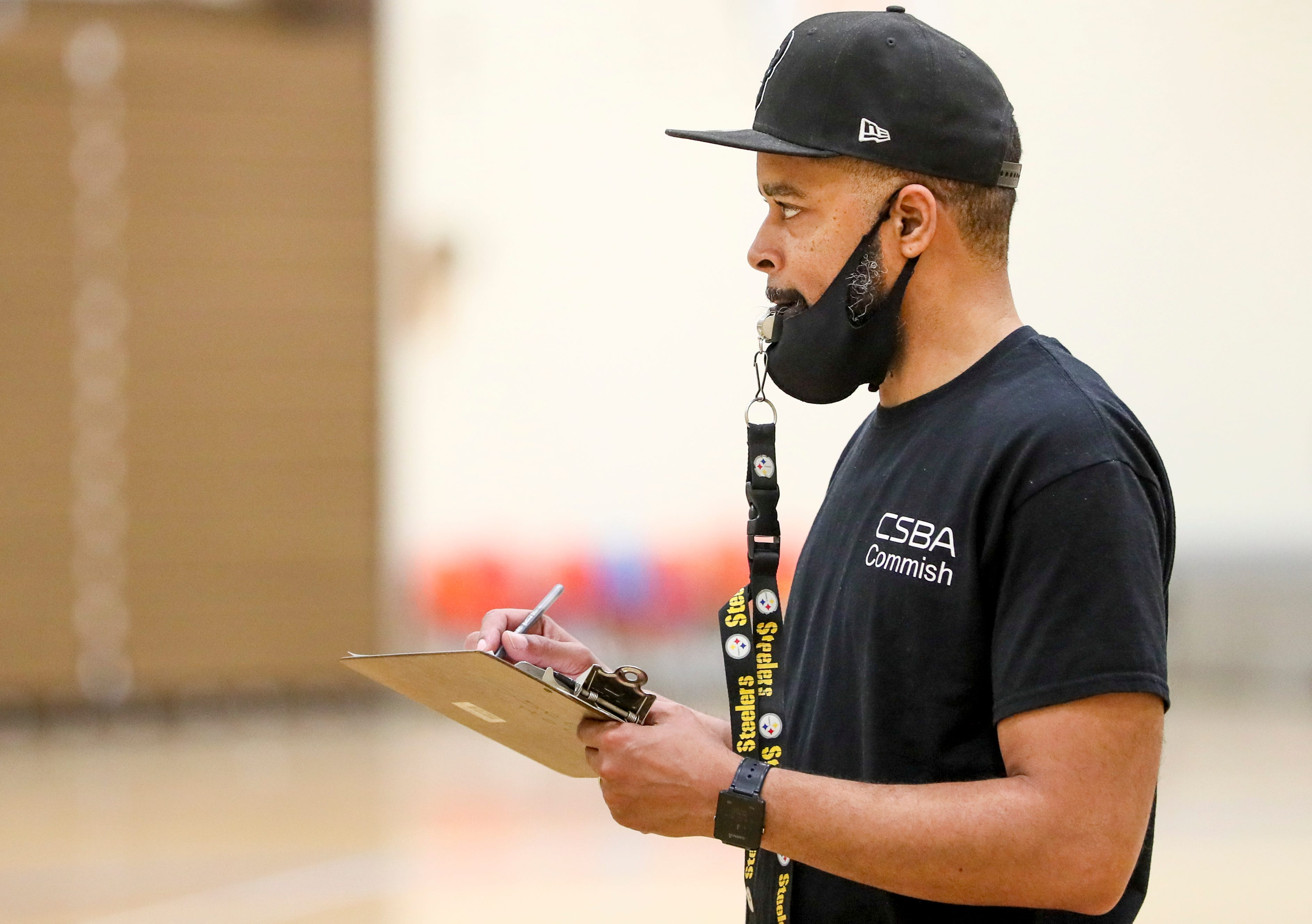 Nigel Harvey, executive director of Cream Skills Inc., takes notes as players try out for a Milwaukee basketball league April 27, 2021, at North Division High School.