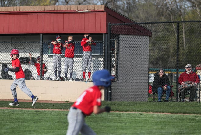 Glendale Little League Cardinals watch their teammates  run to first base and home April 23, 2021.