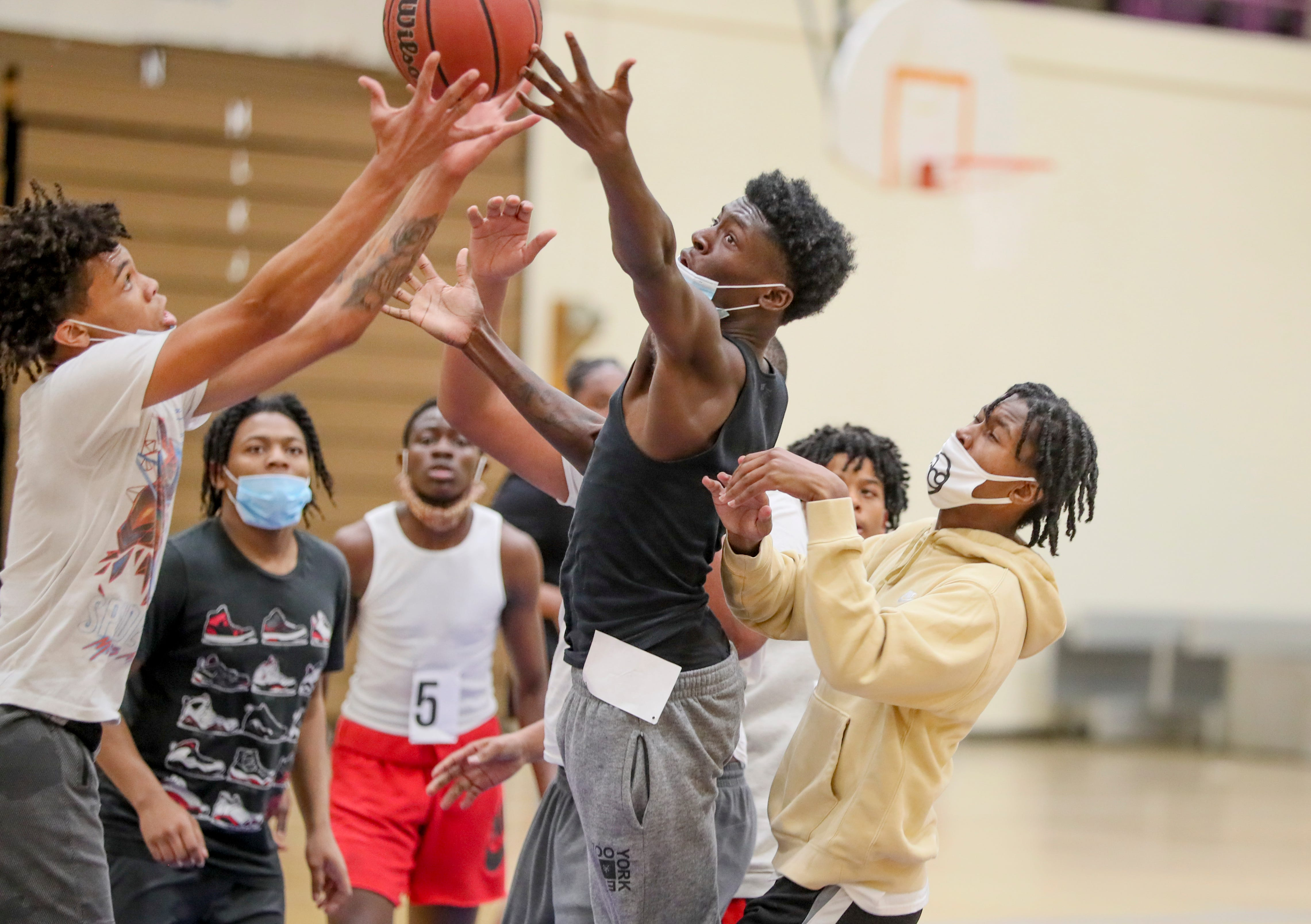 Tahjhe Johnson, left, and players fight for the ball during a scrimmage after tryouts with Cream Skills Inc., a Milwaukee basketball league, on April 27, 2021, at North Division High School in Milwaukee.