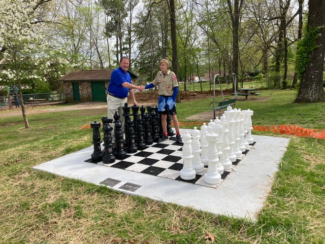 Mayor Hillrey Adams and Zane Darracq stand on the Scout's Eagle project, a giant chess set in Hickory Park.