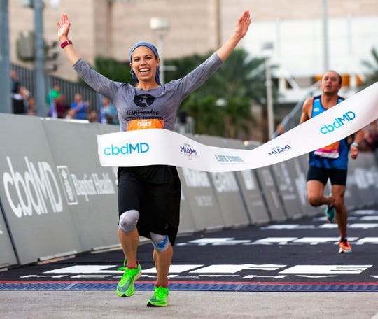 """Beatie Deutsch crossing the finish line at the Miami half marathon. """"I see my belief pushing me forward,"""" she says in a new ad campaign for Adidas."""