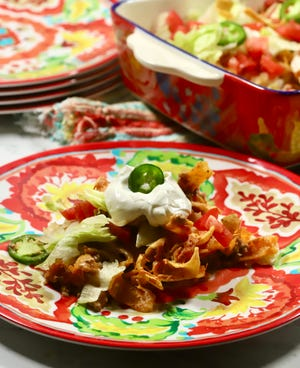 The Walking Taco Casserole is an expansion to the street tacos made with small bags of Fritos or Doritos topped with taco meat, lettuce, tomato, and cheese.
