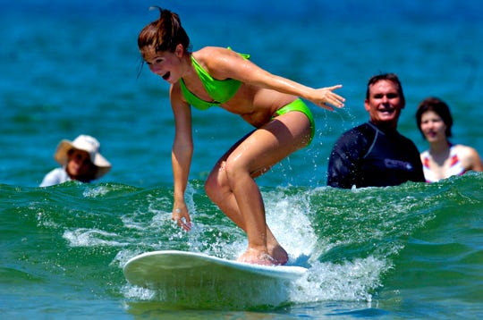 Courtney Beal, 15, of Hiram, GA, rides a wave in under the instruction of the Rev. Edward Fredryk (back right) at Fort Pierce Inlet State Park on July 6, 2005.  Beal and a group of volunteers with World Changers took advantage of one day off from rebuilding homes to learn how to surf.
