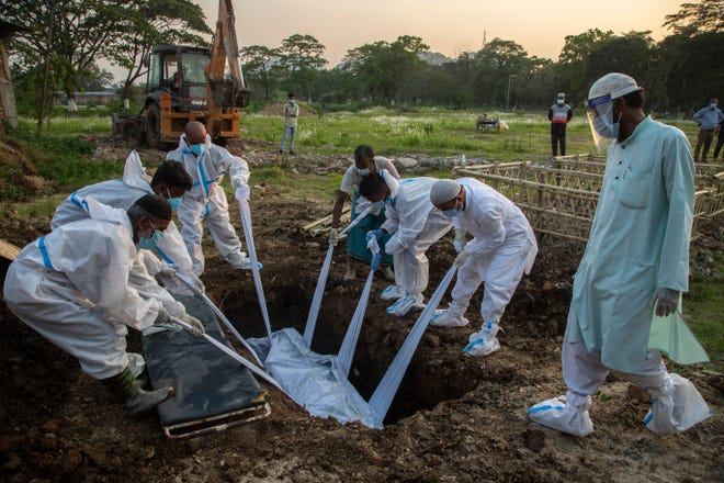 Relatives and municipal workers in protective suit bury the body of a person who died due to COVID-19 in Gauhati, India, Sunday, April 25, 2021.