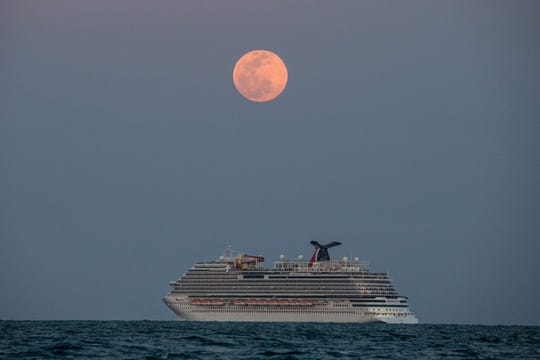 The Carnival Vista cruise ship sails during the Pink Full Moon at Miami Beach on April 26, 2021.