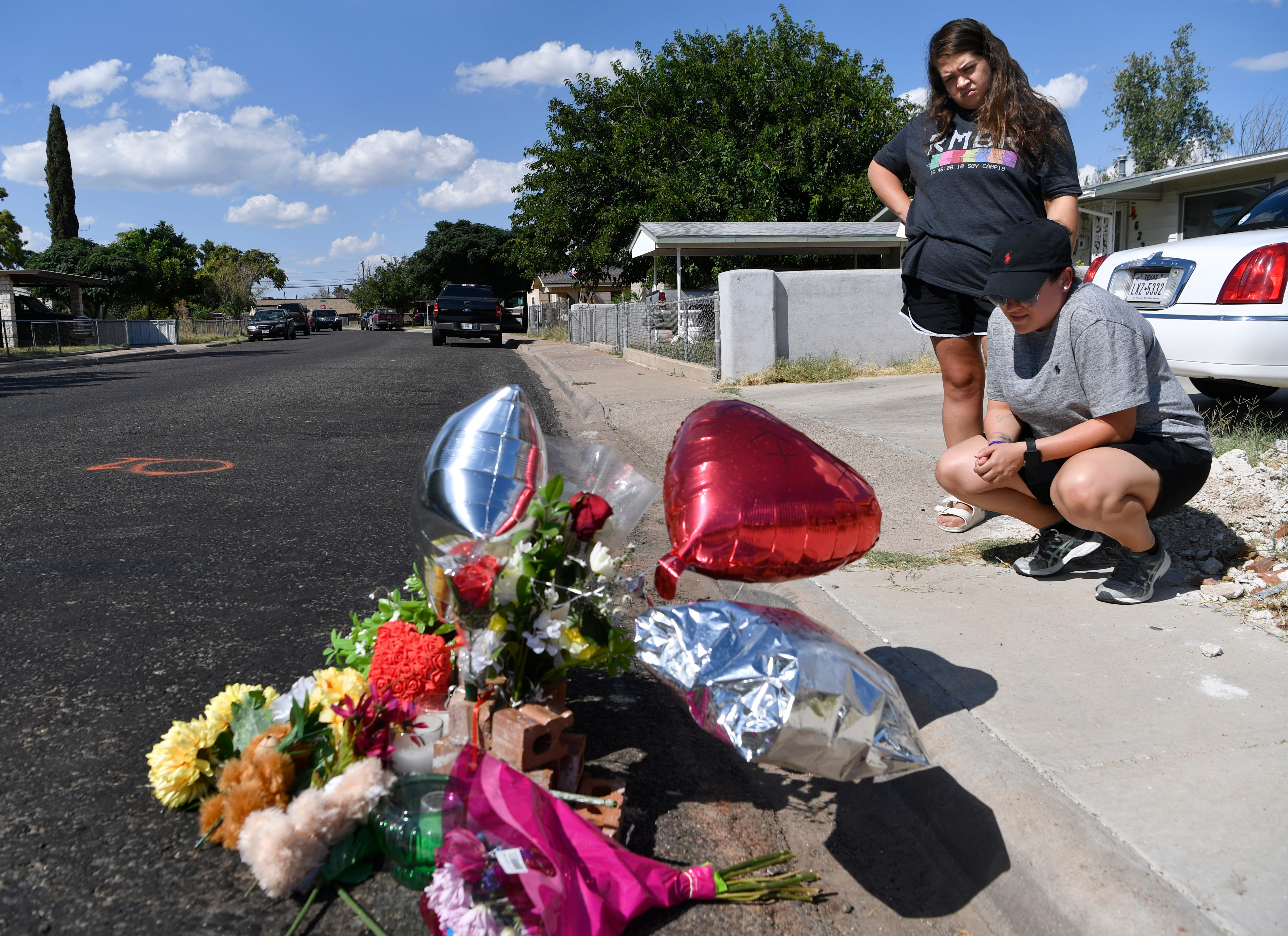 Ashley Salazar, right, and Alyssa Baeza, both of Midland, Texas, pray over a memorial to slain postal worker Mary Granados in Odessa on Sept. 2, 2019. The letter carrier was one of seven killed by Seth Aaron Ator, 36, who went on a shooting spree and struck nearly two dozen people with gunfire.