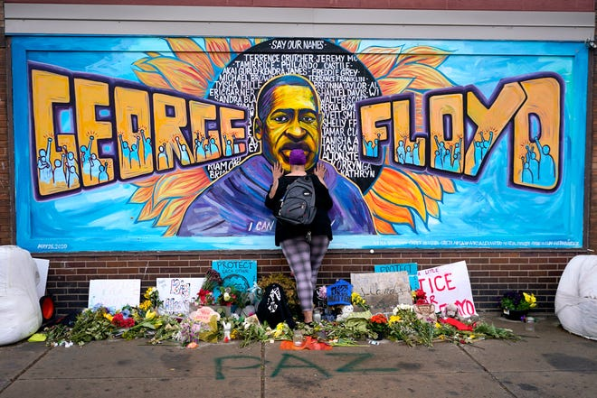 Damarra Atkins pays respect to George Floyd at a mural at George Floyd Square on April 23, 2021, in Minneapolis.