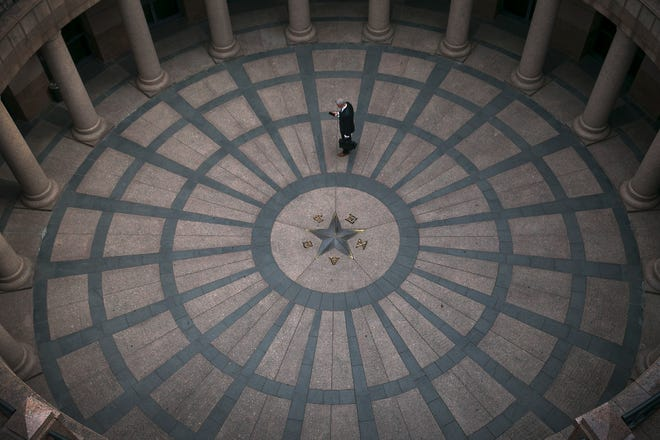 A man works on his smartphone in the outdoor rotunda of the Capitol Extension in this 2017 file photo. [RALPH BARRERA/AMERICAN-STATESMAN]