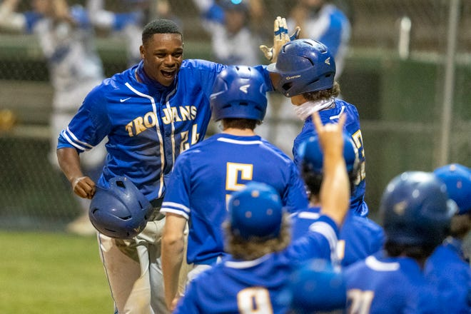 Anderson's Blake Coleman, left, and his teammates celebrate his three-run home run against McCallum during a District 17-5A baseball game at Nelson Field on Tuesday. In a battle between the district leaders, Anderson won 9-3 to seize sole possession of first place in the district race.