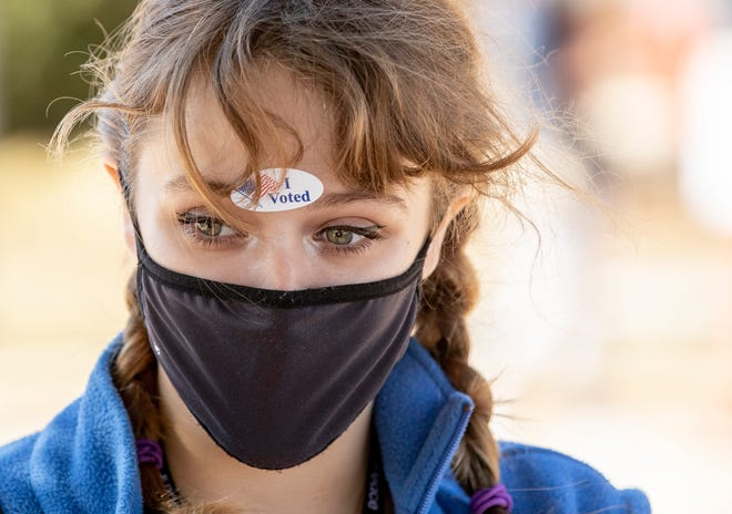 Arielle Shoemaker, 20, shown here Nov. 30, 2020, walks out of the Dan Ruiz Branch Library after voting for the first time.  [JAY JANNER/AMERICAN-STATESMAN]