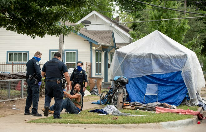 Austin police officers speak Wednesday with a man in a homeless camp at East Cesar Chavez and San Marcos streets in East Austin. Austin voters will go to the polls Saturday to decide whether to bring back a ban on camping in public places.