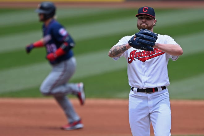 Cleveland starting pitcher Logan Allen waits for Minnesota Twins' Josh Donaldson (20) to run the bases after hitting a solo home run in the first inning of a baseball game, Wednesday, April 28, 2021, in Cleveland. (AP Photo/David Dermer)