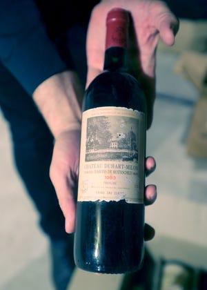 Certified Sommelier Jim Fink holds a bottle of 1983 Bordeaux left behind at the Lehner Community Center in Munroe Falls.