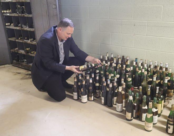 Certified Sommelier Jim Fink looks over wine bottles left behind at the Lehner Community Center in Munroe Falls.