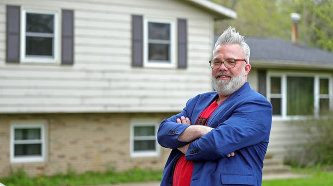 Realtor Eric Cooper stands in front of the Springfield Township house he recently sold using his unique sales strategy of writing humorous descriptions.