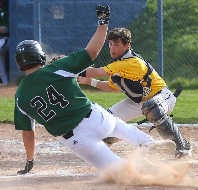 Tallmadge catcher Seth Yacobucci tries to take out Aurora's Ben Fernandez at the plate during the Greenmen's 14-5 win at Tallmadge Tuesday.