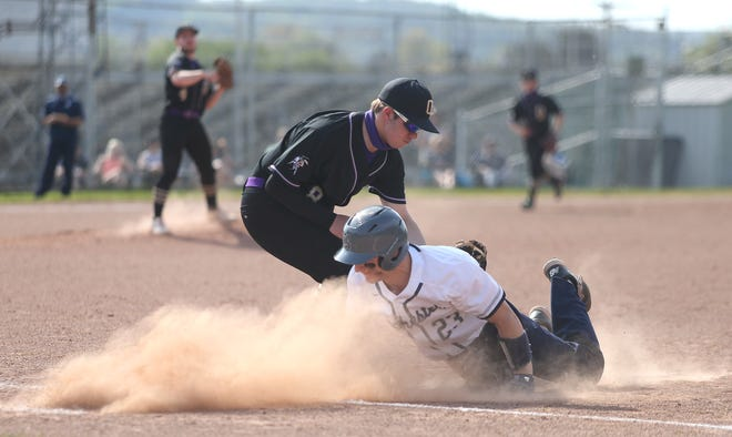 Rochester's Conner Martin (23) dives back to first after a pickoff attempt during the fifth inning Tuesday evening at Rochester High School.