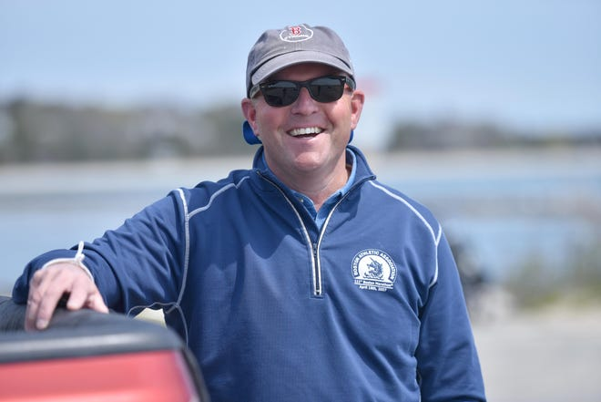 Patrick Clark stands near the spot at Dowses Beach in Osterville where he suffered a heart attack last year. The former Barnstable High School principal had surgery in December to replace a faulty aortic valve.