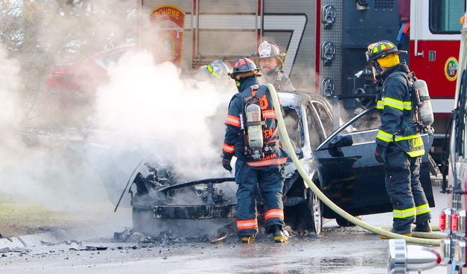 Firefighters attend to a vehicle fire at the base of the Bourne Bridge early Wednesday morning. There were no injuries.