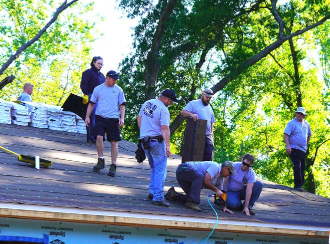 City employee volunteers take to the rooftop to shingle a Habitat for Humanity house in less than a day April 22 in Crestview.
