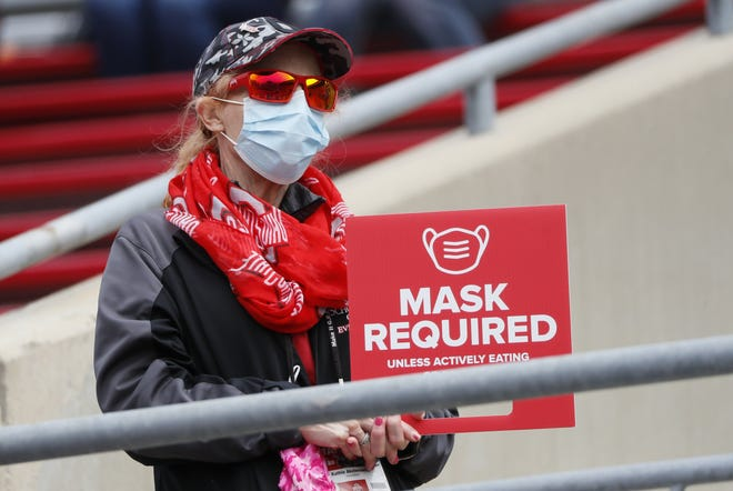 An usher reminds fans of the COVID-19 mask protocols during the Ohio State Buckeyes football spring game at Ohio Stadium in Columbus on Saturday, April 17, 2021.