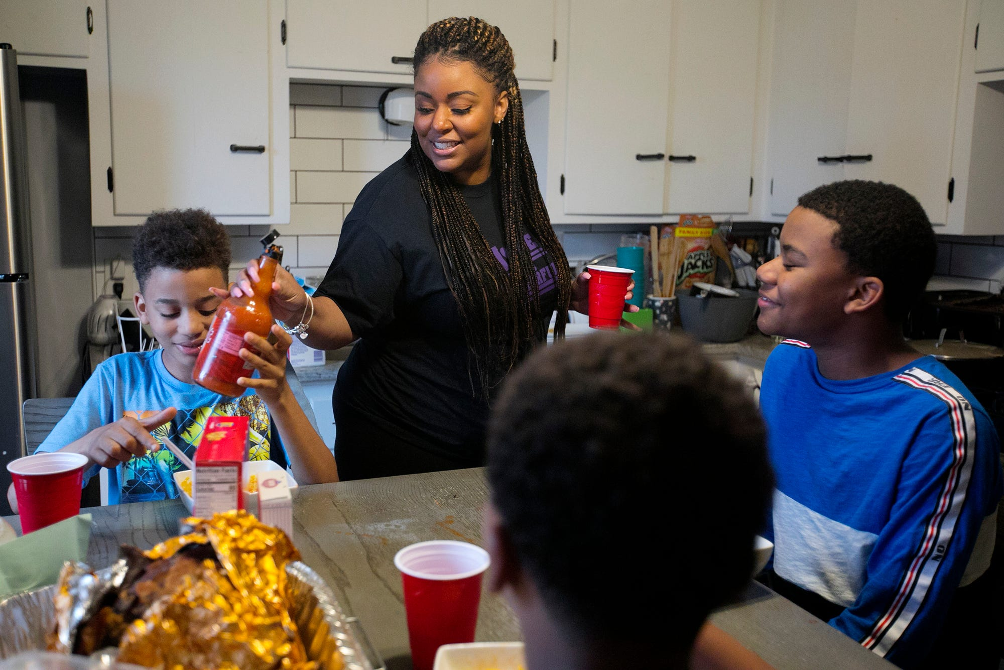 Stevi Knighton makes ramen noodles for her two sons, 10-year-old Ari, left, and 12-year-old Hayden, right, and their friend, Michael Hughes, after school.