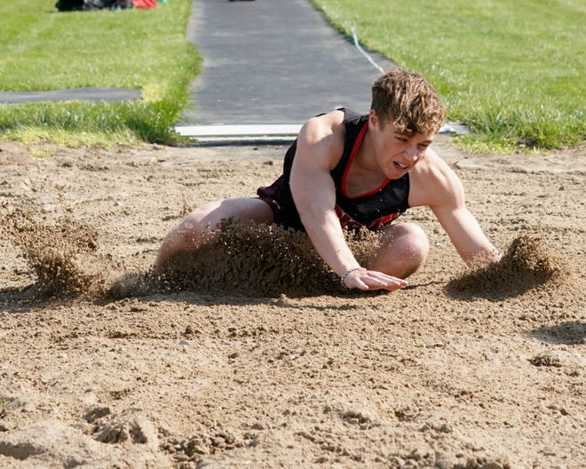 Addison junior Ryan Worsham lands in the sand pit after competing in the long jump event Tuesday afternoon against Hanover-Horton.