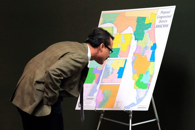 Florida Sen. Rene Garcia, R-Hialeah, scrutinizes a map of proposed congressional districts during a 2012 meeting on redistricting.