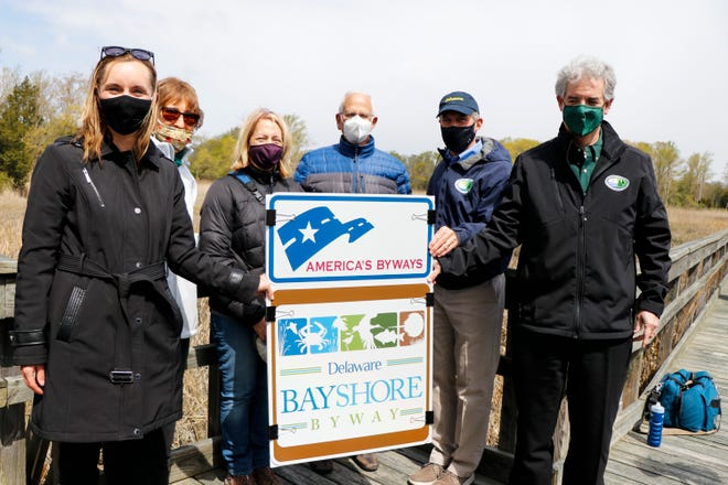 As part of this week's Earth Day celebration, the Delaware Department of Transportation, the Delaware Tourism Office, Delaware Greenways and the Delaware Department of Natural Resources and Environmental Control announced April 26 the Federal Highway Administration has designated the Delaware Bayshore Byway as a National Scenic Byway.  From left: DelDOT Secretary Nicole Majeski; Ann Gravatt, Karen Bennett with DNREC Division of Fish and Wildlife; Chair of the Byway Management Team Steve Borleske; Gov. John Carney and DNREC Secretary Shawn M. Garvin unveiling National Scenic Byways sign at the Delaware National Estuarine Research Reserve's St. Jones Reserve in Dover