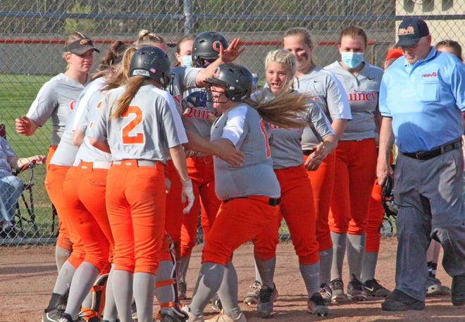 Quincy's Payton Gross is welcomed at home plate by her teammates after her third inning home run to deep left field versus Homer on Tuesday