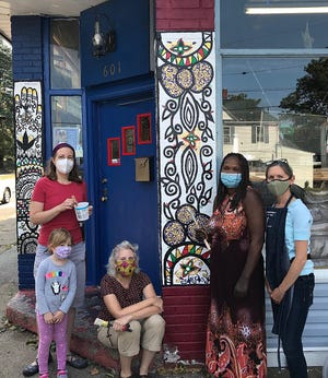 Henna artist Nialwak Athow, second from right, shows off her mural on Lake Erie International Market, 601 Brown Ave. With her are Kelly Armor, center, folklorist in residence for Erie Arts & Culture, which received a grant for the project; Mary Elizabeth Meier, left, art education professor at Edinboro University, and her daughter, Abigail Meier; and Jennifer Peters, art educator in the Fort LeBouef School District. Mary Elizabeth Meier and Peters helped with the mural.