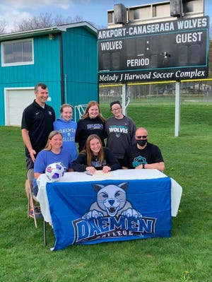Julia Payne signs her letter of intent to Daemen as her parents, Jen and Roger, sisters, Reece and Jacey, and her coaches, John and Jess Lieb look on.