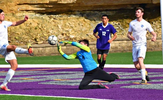 Burlington High School freshman goalkeeper Cayden Lowyery deflects a Davenport North shot in the first half of a non-conference soccer match at Bracewell Stadium Tuesday night. Burlington's Teriq Brown (12) watches.