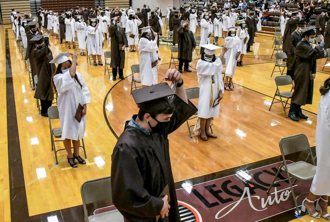 Jared Arellano, foreground, helps lead the Class of 2020 in turning their tassels during the Arts and Communications Academy graduation in July at Garden City High School. The commencements for the Class of 2021 will be held on May 22.