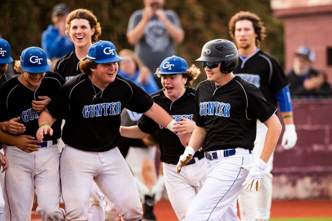 Gunter's Colton Jolly is met by his teammates at the plate after hitting a two-run homer in the Tigers' victory over Bells in the District 11-3A finale.