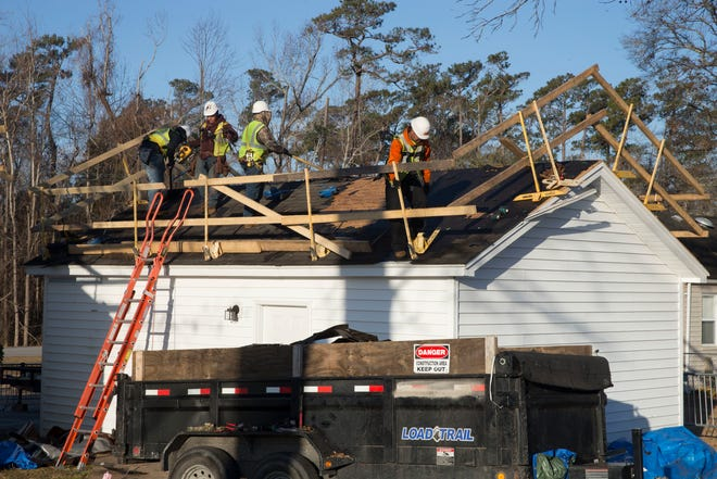 Workers repair a roof at a home on Marine Corps Base Camp Lejeune in February 2019 that was damaged by Hurricane Florence in September 2018.