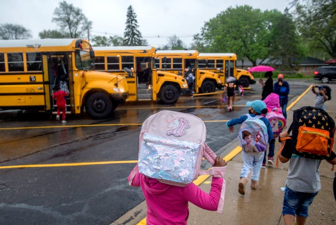 Grade-schoolers use their backpacks to keep the pouring rain off as they head to their buses after school Wednesday, April 28, 2021 at Hines Primary School in Peoria.