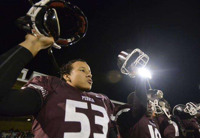 Kendrick Green (53) and fellow Peoria High teammates raise their helmets for the kickoff of a 2013 game with Galesburg.