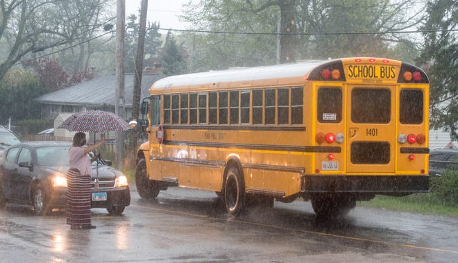 Hines Primary School principal Marcia Lough waves to students in a steady downpour as they head home on a bus Wednesday, April 28, 2021 in Peoria.