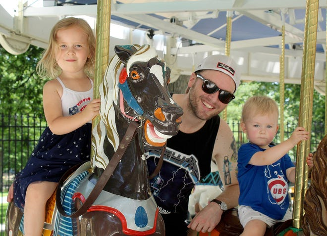 Mike Marten, center, enjoys a ride on the carousel with his children Eileen, left, and Fitzpatrick in 2020 at Krape Park in Freeport.