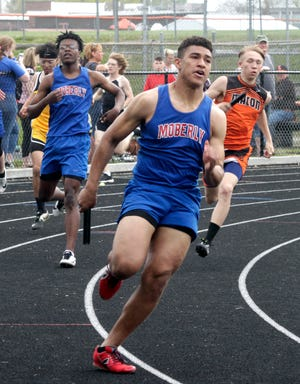 Upon receiving the baton from Mar'sean Winn, left, Moberly senior Jacksyn Miller grips the stick as he jets off running the third leg of the boys 4x200m relay race Tuesday during the Gerald Mansfield Track Invitational held at Macon. Miller and his Spartans comrades placed second in this event, and the same group won the 100m relay.
