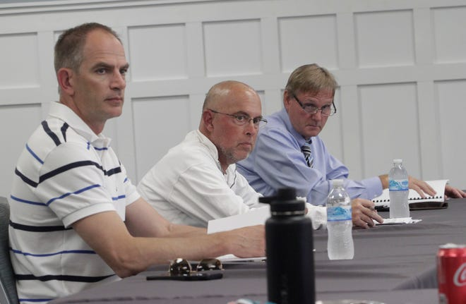 Moberly Area Community College Board of Trustee members Brad Goessling, left, David Weis and John Cochran, right, pay attention to a monthly financial report shared during a Monday, April 26 board business meeting held at the college.
