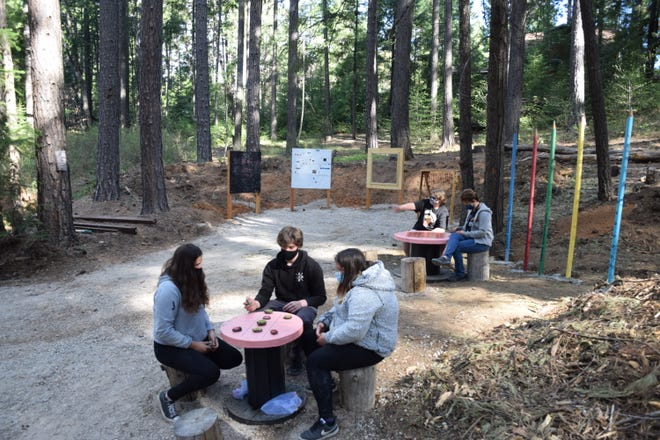 Dunsmuir Elementary School students sit in one of the new outdoor classrooms created this semester for outside learning.