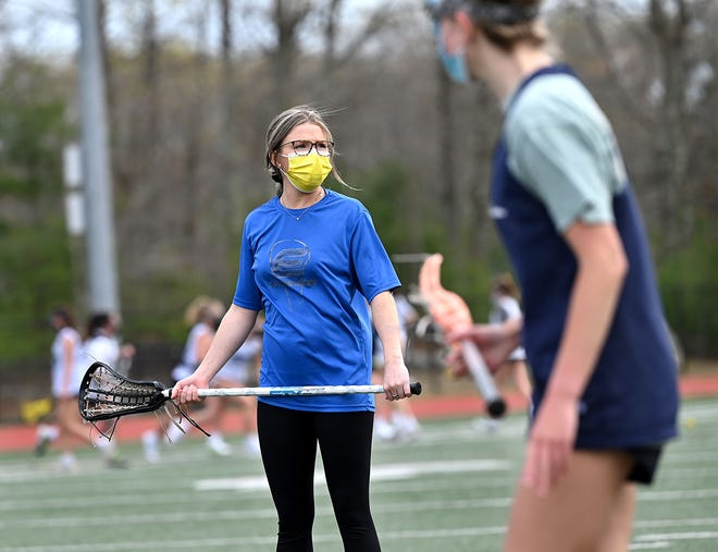 Medway's new girls lacrosse coach, Milford native Olivia Overdahl, watches her players  practice at Medway High School, April 28, 2021.  Overdahl graduate from Westfield State in 2019.