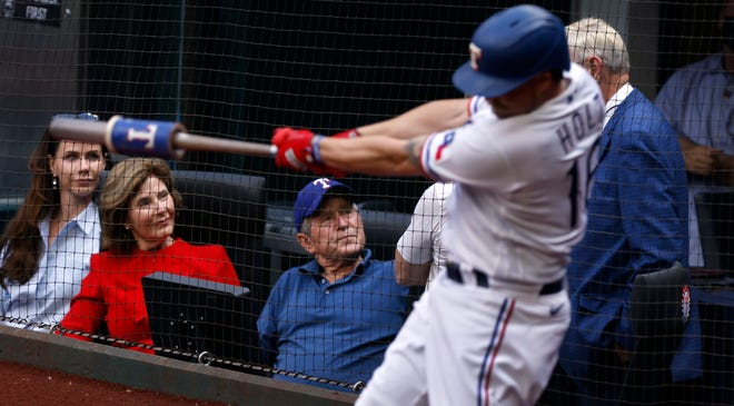 Former President George W. Bush, center, visits with Rangers co-owner Ray Davis on April 5 as he sits in a field level suite with wife Laura Bush and daughter Barbara Bush during Opening Day at Globe Life Field in Arlington, Texas. (TNS)