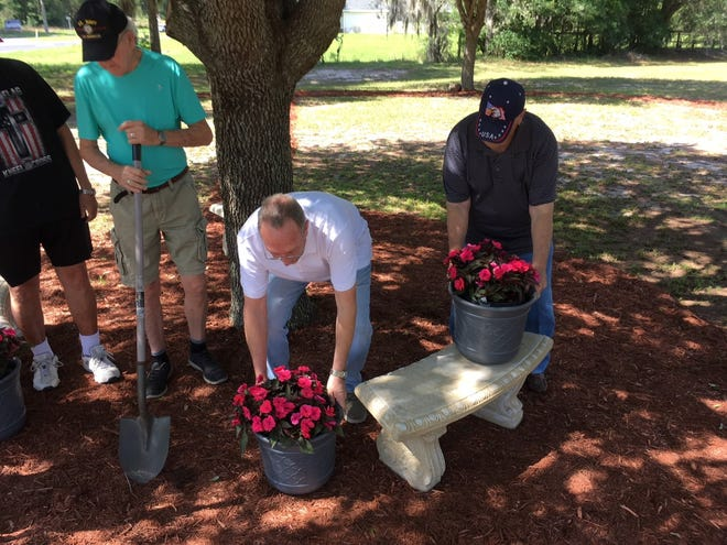 From left to right, Ken Lawlor, with shovel; Senior Pastor Ray Westman, with flowers; and Wayne Richardson with flowers on bench work at the new prayer park in southwest Ocala. The opening ceremony will be on May 6, the National Day of Prayer.