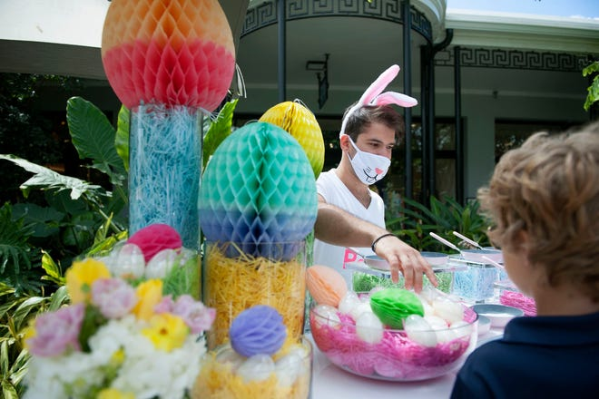 Aposay Minan, wearing a mask outdoors, gives out eggs during The Royal Poinciana Plaza A Royal Easter Affair for the Little Peeps event held April 3.