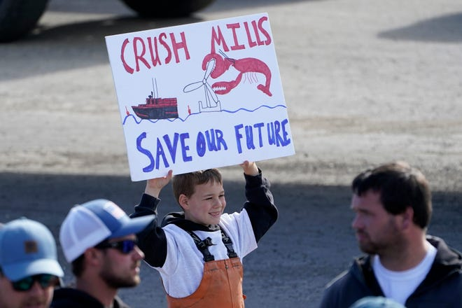 A boy holds a sign at a rally to protest Maine Gov. Janet Mills' support for offshore wind projects, Wednesday, April 28, 2021, in Augusta, Maine.