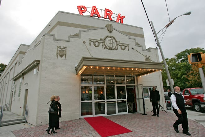 Patrons enter the theater with its restored sign in lights on Oct. 23, 2009. An auction of the property scheduled for Thursday was postponed.